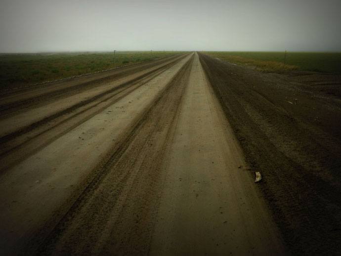 Muddy dalton highway stretching off into the misty distance